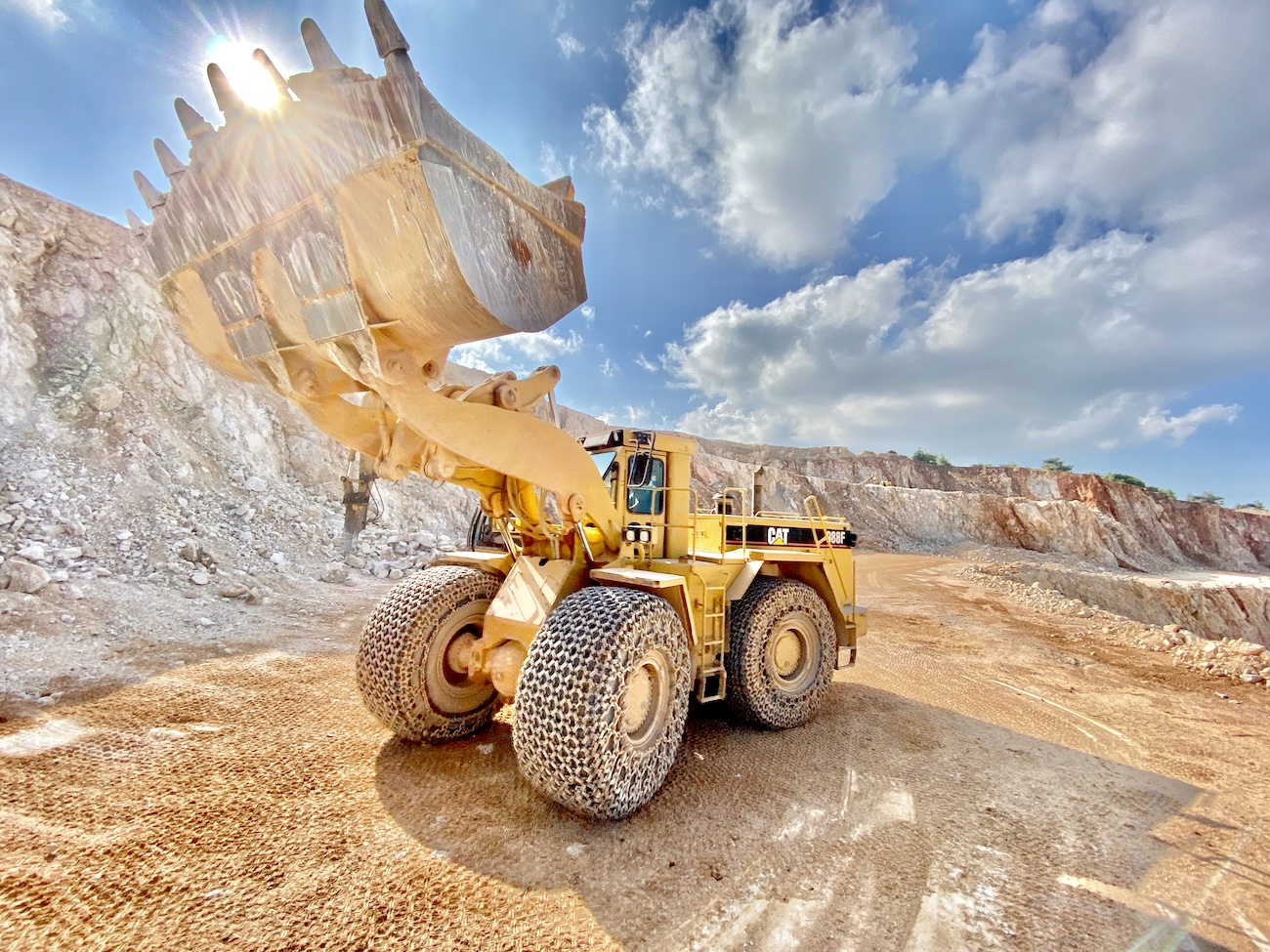 excavator in quarry and clouds
